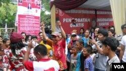 Anak-anak di bawah umur tertegun menyaksikan goyangan artis dangdut dalam kampanye PKPI di Jakarta, 17 Maret 2014 (VOA/Andylala)