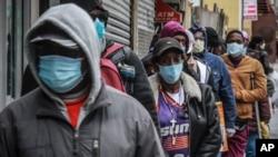 纽约哈莱姆区居民排队领取口罩和食物。(美联社2020年4月18日摄)