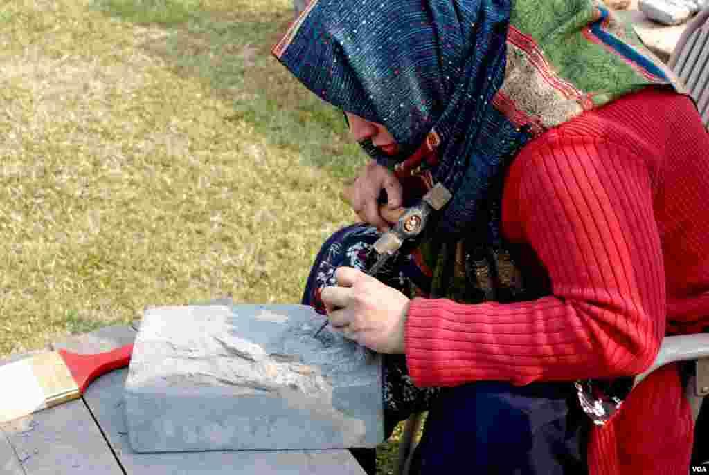 ایک طالبہ پتھر پر تصویر نقش کرنے میں مصروف ہے۔
