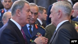 FILE - Turkish Defense Minister Hulusi Akar, left, speaks with U.S. Defense Secretary Jim Mattis prior to a defense ministerial meeting at NATO headquarters in Brussels, Oct. 4, 2018.