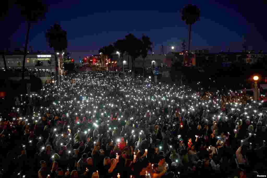 지난 4일(현지시간) 미국 캘리포니아주 맨해튼비치에서 진행된 라스베이거스 총기난사 희생자 추모식 현장. 시민들이 함께 촛불과 휴대전화 조명을 들어올리고 있다.