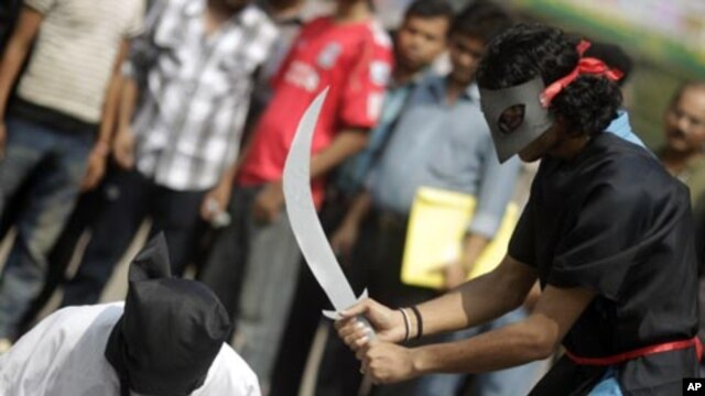 Members of Magic Movement, a group of young Bangladeshis, stage a mock execution scene in protest of Saudi Arabia beheading of eight Bangladeshi workers in Dhaka October 15, 2011.