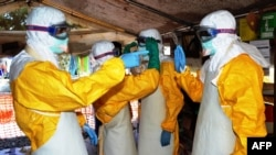 FILE - Guinea's health workers wearing protective suits join members of the Medecins sans frontieres Ebola treatement center near the main Donka hospital in Conakry on Sept. 25, 2014.