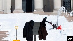 Petugas membersihkan salju di Washington.