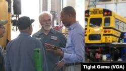 Tashitaa Tufaa chats with mechanics and drivers at Metropolitan Transportation Network's maintenance shop in Fridley, Minnesota, Aug. 10, 2017.