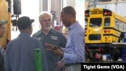 미국의 스쿨버스 회사 MTN의 최고경영자인 타시타 투파 대표(오른쪽)가 미네소타주 프리들리시의 회사 정비공장에서 직원들과 대화하고 있다.