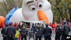 "Petugas kepolisian berdiri dekat balon raksasa karakter Olaf dari film animasi ""Frozen"" yang sedang diisi gas untuk Parade Hari Bersyukur atau Thanksgiving di New York, 22 November 2017."