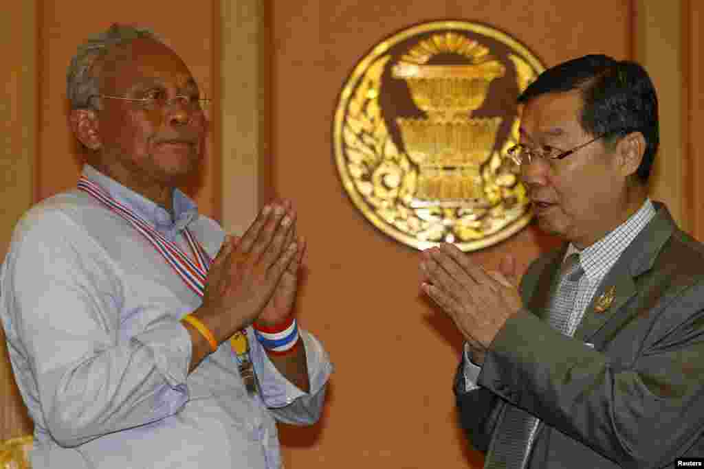 Newly elected Senate Speaker Surachai Liengboonlertchai (right) and anti-government protest leader Suthep Thaugsuban greet each other in parliament, Bangkok. May 12, 2014.