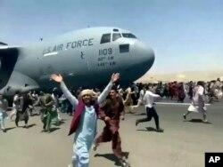 Ratusan orang berlari di samping pesawat Angkatan Udara AS saat bergerak di landasan bandara internasional, di Kabul, Afghanistan, Senin, 16 Agustus. 2021. (Foto: AP)