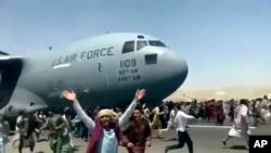 在阿富汗喀布尔国际机场,数百人在一架美国空军C-17运输机的跑道上奔跑。在塔利班进驻了喀布尔后,他们试图逃离这里。(202年8月16日)