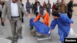 Medical personnel wheel body of victim killed by suicide bomber in Tuz Khurmato city, Jan. 23, 2013