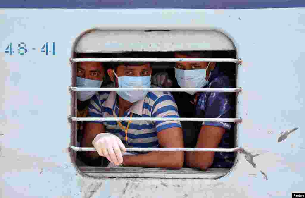 Migrant workers, who were trapped in the western state of Rajasthan due to a coronavirus lockdown, look out from a train upon their arrival in their home state of eastern West Bengal, India.