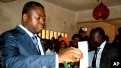 President of Togo Faure Gnassingbe (à gauche) place un bulletin de vote dans l'urne lors de l'élection présidentielle, à Lomé, le 25 juillet 2013