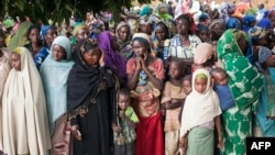 FILE - Refugees from Central Africa wait in Garoua Boulaye, Cameroon, for food and clothes delivered by humanitarian associations, April 25, 2014.