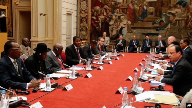 "French President Francois Hollande, right, talks during the round table photo at the ""Paris' Security in Nigeria summit"", at the Elysee Palace, in Paris, May 17, 2014."