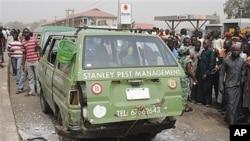 People surround a minibus struck in apparent explosion near highway overpass in Kaduna, Nigeria, Feb. 7, 2012.