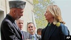 ລັດຖະມົນຕີການຕ່າງປະເທດສະຫະລັດ ທ່ານນາງ Hillary Clinton ຈັບມືກັບປະທານາທິບໍດີອັຟການິສຖານ ທ່ານຮາມິດ ກາໄຊ (20 ຕຸລາ 2011)