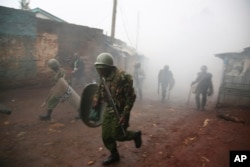 Riot police are caught in tear gas during running battle with opposition supporters in Kibera Slums in Nairobi, Kenya,Oct. 26, 2017.