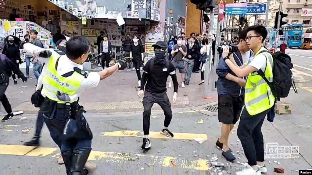 Ảnh chụp lại từ video trên mạng xã hội cho thấy một viên cảnh sát chĩa súng nhắm vào một người biểu tình ở Sai Wan Ho, Hong Kong, ngày 11/11/2019. CUPID PRODUCER via REUTERS