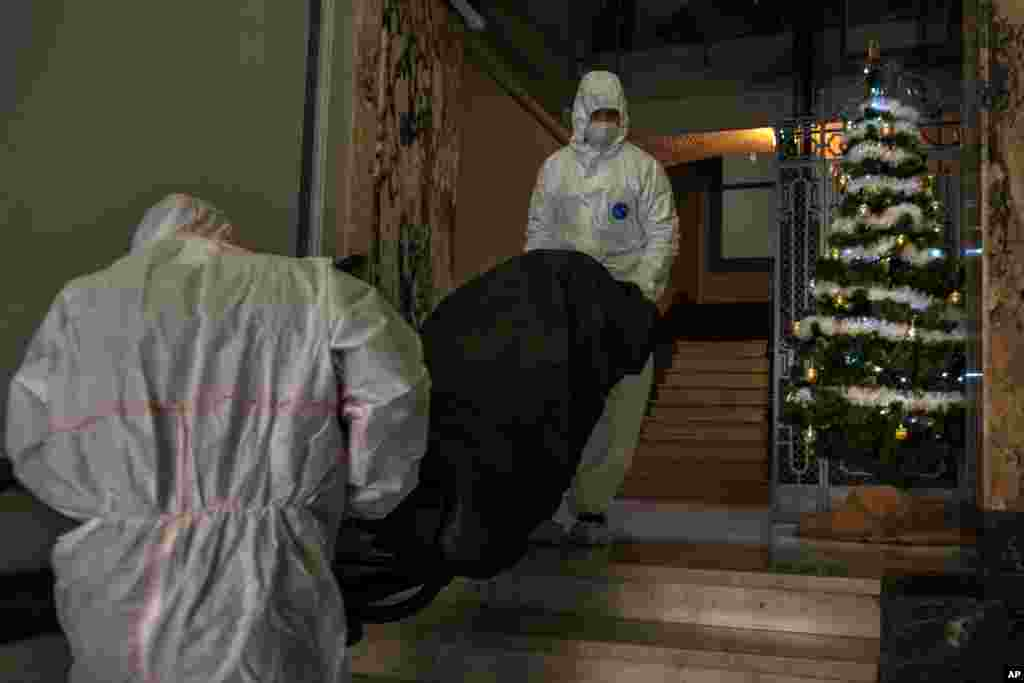 Mortuary workers remove the body of an elderly person who died of COVID-19 from a nursing home in downtown Barcelona, Spain.