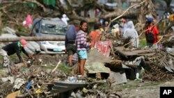 Seorang penyintas berdiri di tengah sampah di Tacloban, Filipina tengah (8/12). (AP/Aaron Favila)