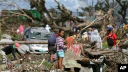 Para korban berdiri di antara reruntuhan akibat topan Haiyan di Tacloban, Filipina Tengah, 8 Desember 2013. FIFA menawarkan bantuan $1 Juta untuk perbaikan lapangan sepakbola akibat topan itu.