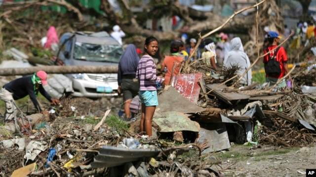 A typhoon survivor stands on rubbish in Tacloban, central Philippines, Dec. 8, 2013.