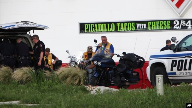 FILE - Police detain members of two motorcycle gangs after a shootout at Twin Peaks restaurant in Waco, Texas, May 17, 2015.