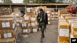 FILE - A police officer keeps guard over electoral materials still stacked in boxes at the offices of the Independent National Electoral Commission in Kano, in northern Nigeria, Feb. 16, 2019.