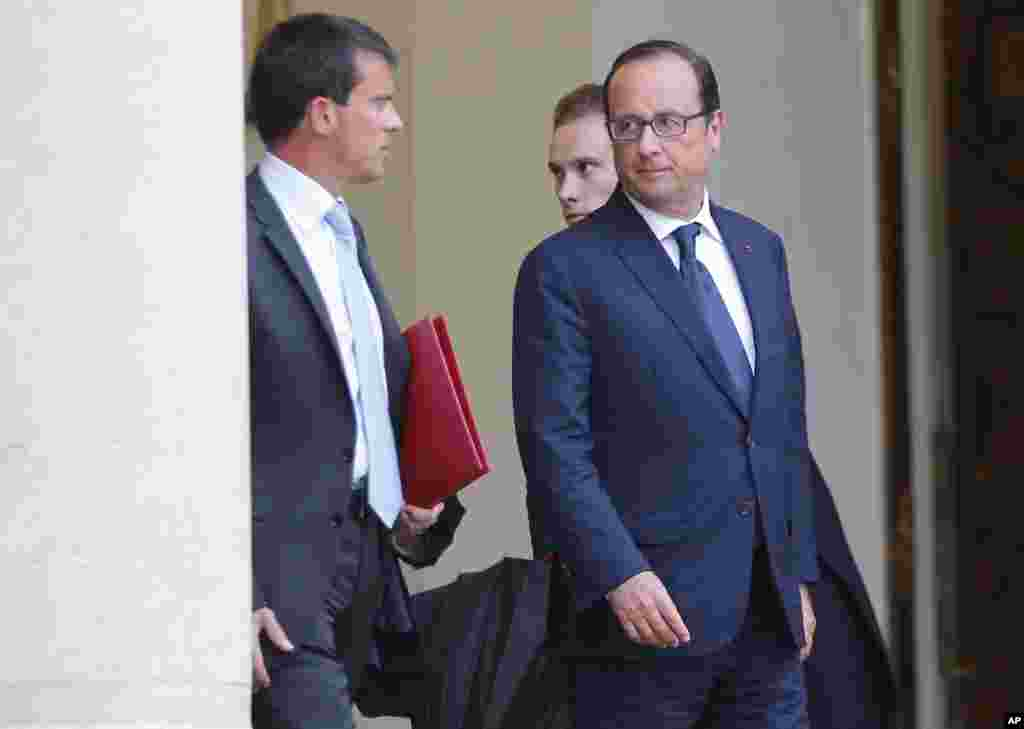 French Prime Minister Manuel Valls, left, leaves with French President Francois Hollande after a meeting at the Elysee Palace in Paris, Aug. 25, 2014.