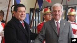 FILE - Paraguay's outgoing President Horacio Cartes receives Uruguay's President Tabare Vazquez, at the 52nd Mercosur Summit in Luque, Paraguay, June 18, 2018.