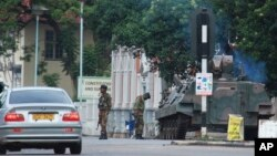 A military tank is seen with armed soldiers on a road leading to President Robert Mugabe's office in Harare, Zimbabwe, Nov. 15, 2017.