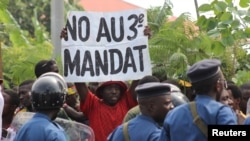 A protester holds a placard at a rally opposing Burundi President Pierre Nkurunziza's bid for a third five-year term in office, in Bujumbura, May 4, 2015.