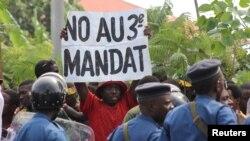 Seorang pengunjuk rasa di Bujumbura, mengangkat kertas berisikan protes menentang keputusan partai yang berkuasa, CNDD-FDD yang memperbolehkan Presiden Pierre Nkurunziza mencalonkan diri menjadi presiden untuk masa jabatan ketiga (4/5).