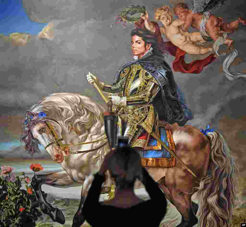 A visitor takes a smartphone picture of the painting 'Equestrian portrait of King Philipp II (Michael Jackson)' from US artist Kehinde Wiley at a preview of the exhibition 'Michael Jackson: On The Wall' at the Bundeskunsthalle museum in Bonn, Germany.