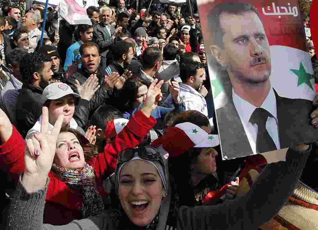 Ciudadanos que apoyan al presidente Bashar al-Assad participan en una manifestación en una plaza en Damasco.