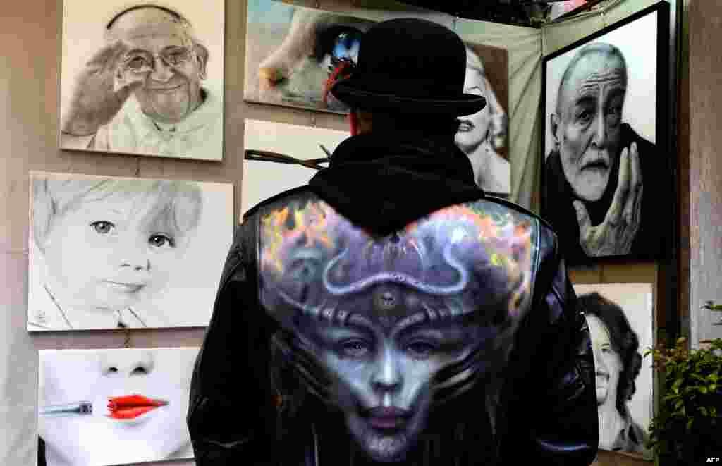 이탈리아 로마의 '비아 마르구타' 예술가 거리에서 한 예술가가 자기 작품을 훝어보고 있다. 비아 마르구타 거리는 조각, 그림, 시, 영화 등 각종 예술 문화의 집합소로서 매년 '100인의 예술가' 전시회가 열린다.