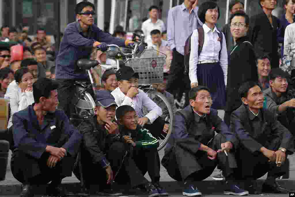 North Koreans react as they watch a movie shown on a huge screen in a public square in the country's capital, Pyongyang.