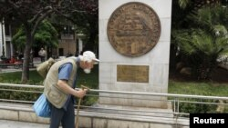 A man makes his way past a replica of a one drachma coin outside the Athens Town Hall, May 21, 2012.