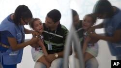 지난 25일 브라질 리우데자네이루의 보건소에서 간호사가 한 여자 어린이에게 신종독감 백신을 주사하고 있다.