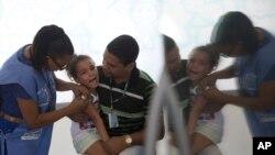 Cette fille reçoit une injection contre le virus de la grippe H1N1 d'une infirmière dans une clinique de Rio de Janeiro, au Brésil, le lundi 25 avril 2016.