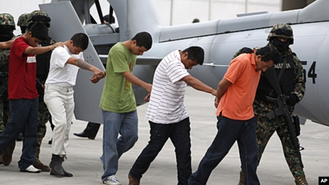 Alleged members of the Zetas cartel are escorted by members of the military as they are presented to the press after their arrests in Mexico City, Oct. 7, 2011.