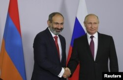 Russian President Vladimir Putin shakes hands with Armenian Prime Minister Nikol Pashinyan during their meeting in Sochi, Russia, May 14, 2018.