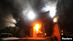 FILE - A U.S. diplomatic compound is seen in flames after an attack by an armed group, in Benghazi, Libya, Sept.11, 2012.
