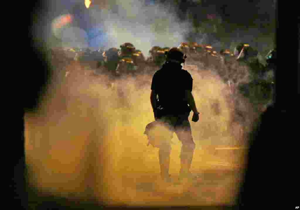 Police fire teargas as protesters converge on downtown following Tuesday's police shooting of Keith Lamont Scott in Charlotte, N.C., Sept. 21, 2016.