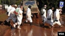 Para pekerja bersiap melakukan pembersihan limbah beracun yang menggenangi jalan-jalan di Devecser, Hungaria barat.