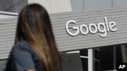 FILE - In this Sept. 24, 2019, file photo, a woman walks below a Google sign on the campus in Mountain View, Calif. New Mexico is suing Google over allegations that the tech company is illegally collecting personal data generated by children in…