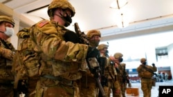 Troops stand in formation inside the visitors center to reinforce security at the Capitol in Washington, Jan. 13, 2021.