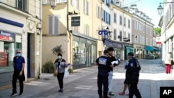 Municipal police officers check documents as they patrol in a street of Sceaux, south of Paris, France, during nationwide confinement measures to counter the Covid-19, April 8, 2020.