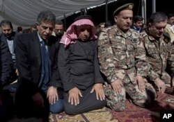 Safi al-Kaseasbeh, third right, father of slain Jordanian pilot, Lt. Muath al-Kaseasbeh attends a mass funeral at the Kaseasbeh tribe's gathering divan at their home village of Ai, near Karak, Jordan, Feb. 4, 2015.
